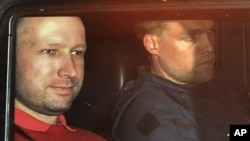 Norway's twin terror attacks suspect Anders Behring Breivik, left, sits in an armored police vehicle after leaving the courthouse following a hearing in Oslo, July 25, 2011.