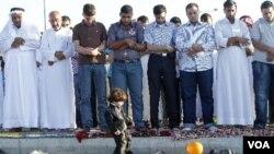 Seorang anak kecil bermain dengan balon di depan para pria Suriah yang sedang sholat Idul Fitri berjamaah di luar Kedutaan Suriah di Amman, Yordania, Selasa (30/8).