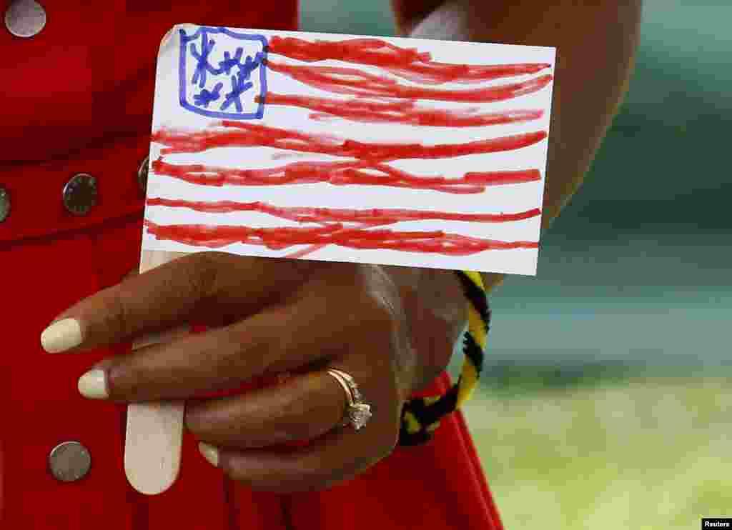 Đệ nhất phu nhân Michelle Obama cầm một lá cờ Mỹ do một em nhỏ vẽ trong chuyến thăm một đơn vị đồn trú của quân đội Mỹ tại Vicenza, miền bắc nước Ý.