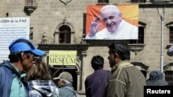 FILE - Pedestrians walk at San Francisco square where an image of Pope Francis is displayed in La Paz, Bolivia, June 30, 2015.