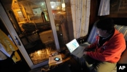 David C. Bond of Wickford, R.I. checks weather forecasts on his computer while riding out Sandy on his boat docked in Annapolis, Md. Monday, Oct. 29, 2012. Sandy continued on its path Monday, as the storm forced the shutdown of mass transit, schools and f