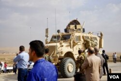 Iraqi Christians on the outskirts of the town of Bartilla watch Iraqi military vehicles advancing. Most Christians have been blocked from visiting their homes with Iraqi military officials saying the area remains unsafe, Bartilla, Iraq, Oct. 31, 2016. (J. Dettmer/VOA)