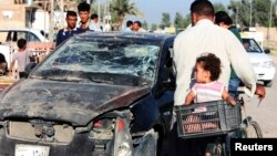 Residents pass by a damaged vehicle a day after a bomb attack in central Baquba, 65 km northeast of Baghdad, Aug. 25, 2013.