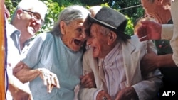 Paraguayan Anacleto Escobar (R) and his wife Cayetana Roman, smile during a ceremony coinciding with his 100th birthday in which they received a house.