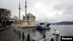 A worker sprays disinfectant outside Ortakoy Mosque to prevent the spread of coronavirus disease in Istanbul, Turkey, March 23, 2020.