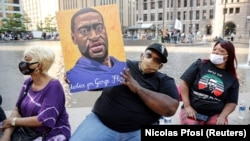 """Jerlano Bell of North Carolina holds up a George Floyd sign at the """"One Year, What's Changed?"""" rally hosted by the George Floyd Memorial Foundation to commemorate the first anniversary of his death, outside the Hennepin County Government Center"""