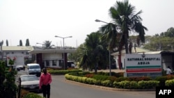 FILE - A man walk past signage for the National Hospital in Abuja, Nigeria, Jan. 14, 2016.