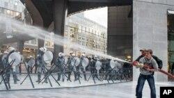 Evropski mlekari prskaju policiju mlekom iz šmrka za vreme demonstracija ispred Evropskog parlamenta u Briselu.