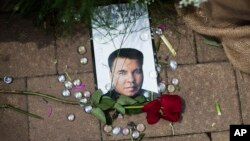 A rose lays next to an image of Muhammad Ali at a makeshift memorial at the Muhammad Ali Center in Louisville, Kentucky, June 5, 2016.