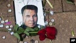لوئیول میں محمد علی سنٹر میں ایک عارضی یادگار پر عظیم باکسر کی تصویر کے باس گلاب کا ایک پھول رکھا ہے۔