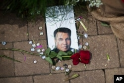 A rose lays next to an image of Muhammad Ali at a makeshift memorial at the Muhammad Ali Center, June 5, 2016, in Louisville, Ky. Ali, the heavyweight champion whose fast fists and irrepressible personality transcended sports and captivated the world, die
