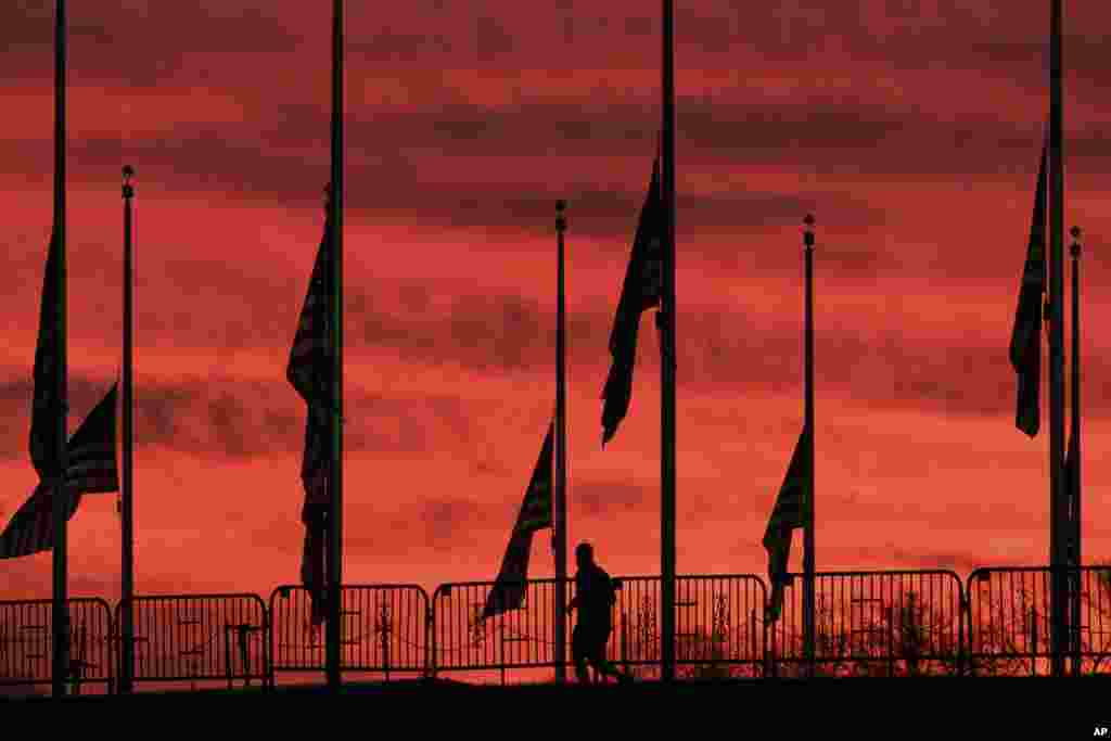 A solitary runner passes under the flags hanging at half-staff surrounding the Washington Monument at day break in Washington, D.C.