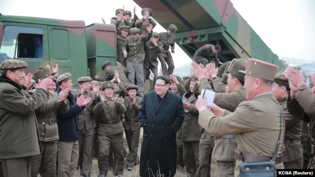 North Korean leader Kim Jong Un, center, guides the test fire of a new multiple launch rocket system in this undated photo released by North Korea's Korean Central News Agency (KCNA) in Pyongyang, March 4, 2016.