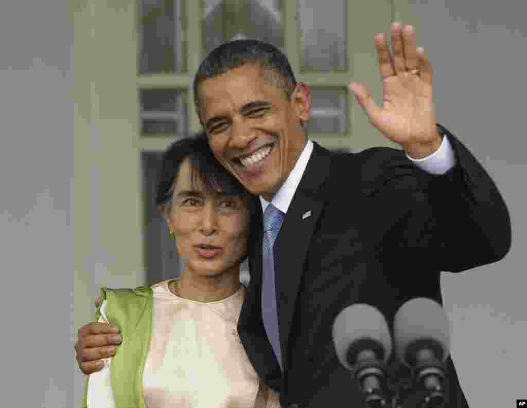 US President Barack Obama, right, waves as he embraces Burmese democracy activist Aung San Suu Kyi after addressing members of the media at her residence in Rangoon, Burma, November 19, 2012.
