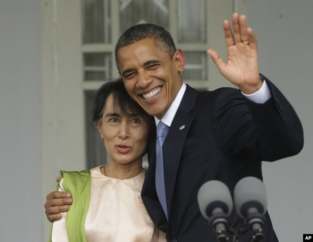 US President Barack Obama (R) waves as he embraces Burmese democracy activist Aung San Suu Kyi after addressing members of the media at Suu Kyi's residence in Rangoon, Burma, November 19, 2012.