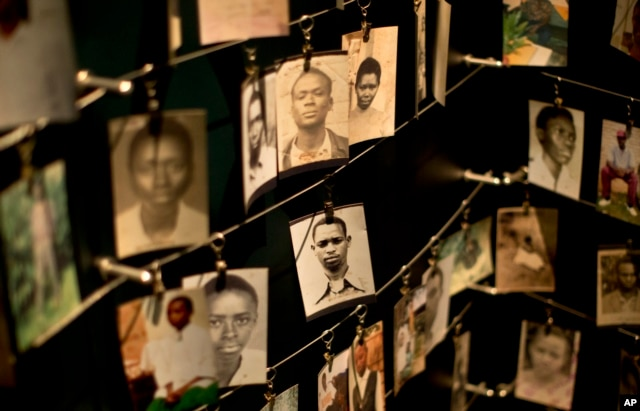 FILE - Family photographs of some of those who died hang in a display in the Kigali Genocide Memorial Centre in Kigali, Rwanda, April 5, 2014.
