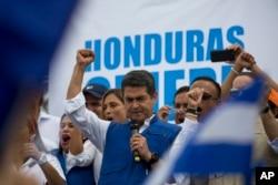 Honduran President Juan Orlando Hernandez raises his right fist as he mets with his party base, in Tegucigalpa, Honduras, Thursday, Dec. 7, 2017.