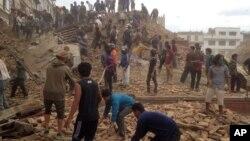 在尼泊尔首都加德满都,强烈地震发生后,志愿者协助救援人员抢救瓦砾下可能生还的人。摄于2015年4月25 日,星期六
