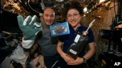 In this photo made available by U.S. astronaut Christina Koch via Twitter on Dec. 26, 2019, she and Italian astronaut Luca Parmitano pose for a photo with a cookie baked on the International Space Station. Researchers want to inspect the handful of…