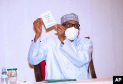 نائجیریا کے صدر ویکسین لگوانے کے بعد اپنا سرٹیفیکٹ دکھا رہے ہیں