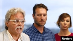 FILE - John Ruszczyk, the father of Justine Damond, speaks as he stands next to his son Jason Ruszczyk and Jason's wife Katarina, during a media conference in Sydney, Dec. 21, 2017.