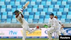 Pakistan's Asad Shafiq bats as England's Jos Buttler looks on during a Pakistan-England match at Dubai International Stadium, United Arab Emirates on Oct. 22, 2105.