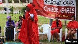 "FILE - A member of the Abuja ""Bring Back Our Girls"" protest group addresses a sit-in demonstration organized by the group at the Unity Fountain in Abuja, Nigeria, June 23, 2014."