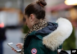 In this Feb. 14, 2019 photo, a woman in New York wears a Canada Goose coat with the hood trimmed in coyote fur. (AP Photo/Frank Franklin II)