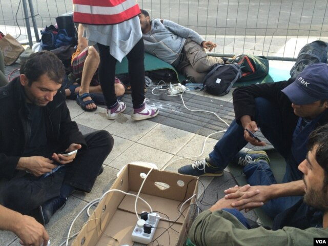 Smartphones help migrants determine routes and sustain vital connections. Aid workers have set up charging stations for them in Vienna, Austria. (H. Murdock/VOA).