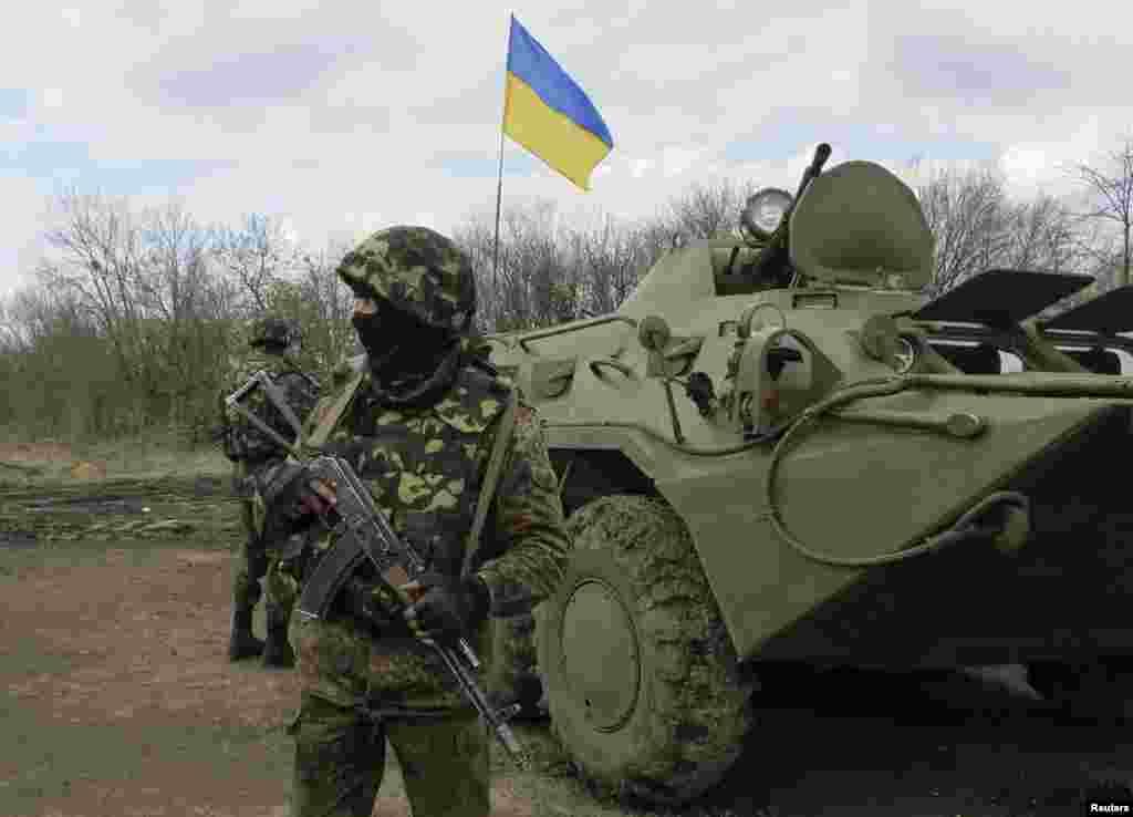 Binh sĩ Ukraine đứng cạnh một xe bọc thép tại trạm kiểm soát gần thị trấn Izium ở miền đông Ukraine.