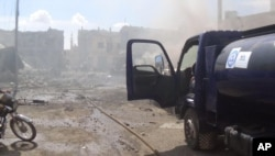 This image taken in Sept. 30, 2015 posted on the Twitter account of Syria Civil Defense, also known as the White Helmets, a volunteer search and rescue group, shows the aftermath of an airstrike in Talbiseh, Syria.