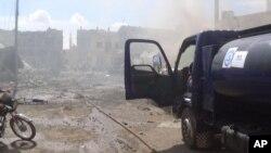 """Hình ảnh được chụp ngày 30/9/2015, đăng trên tài khoản Twitter của tổ chức Phòng vệ Nhân dân Syria, còn được gọi là nhóm """"Những chiếc mũ bảo hiểm trắng"""", một nhóm tình nguyện viên tìm kiếm và cứu hộ, cho thấy hậu quả của một cuộc không kích ở Talbiseh, Syria."""