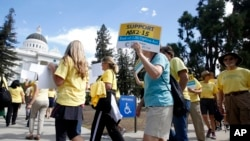 FILE - Activists are seen rallying in support of physician-assisted suicide for the terminally ill at the Capitol in Sacramento, California, Sept. 24, 2015.