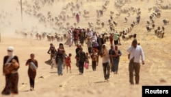 Displaced people from the minority Yazidi sect, fleeing violence from forces loyal to the Islamic State in Iraq's Sinjar town, walk towards the Syrian border, near the Syrian border town of Elierbeh.