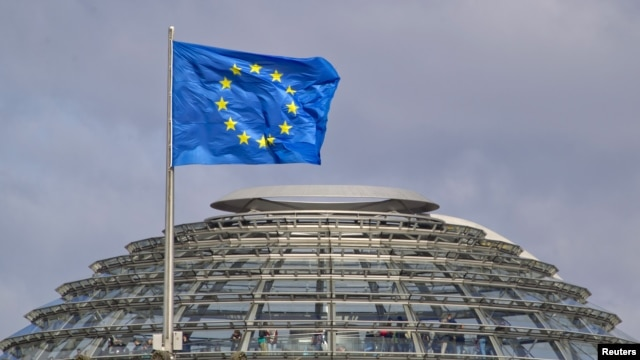 The European Union flag is seen above the cupola of the Reichstag building, the seat of the Bundestag in Berlin, April 2, 2012.