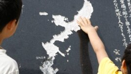 A Okinawa boy touches the map of Okinawa carved on a stone face near the U.S. Marine Corps Air Station Futenma in Ginowan. (File)