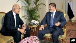 FILE - Nobel Peace Prize winner and one of the leaders of the National Salvation Front, Mohamed ElBaradei (L), meets with Egyptian President Mohammed Morsi, in Cairo, Egypt, November 2012.