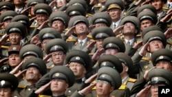 Soldados saludan mientras se entona el himno nacional durante un desfile militar por el 105 aniversario de Kim II Sung, en Pyongyang, Corea del Norte, el 15 de abril de 2017.