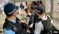 社民连4名成员十一游行途经行人天桥,数十名军装警员沿途包围戒备 (美国之音/汤惠芸)