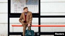一位老者獨自坐在倫敦的公共汽車站。(2013年10月18日)