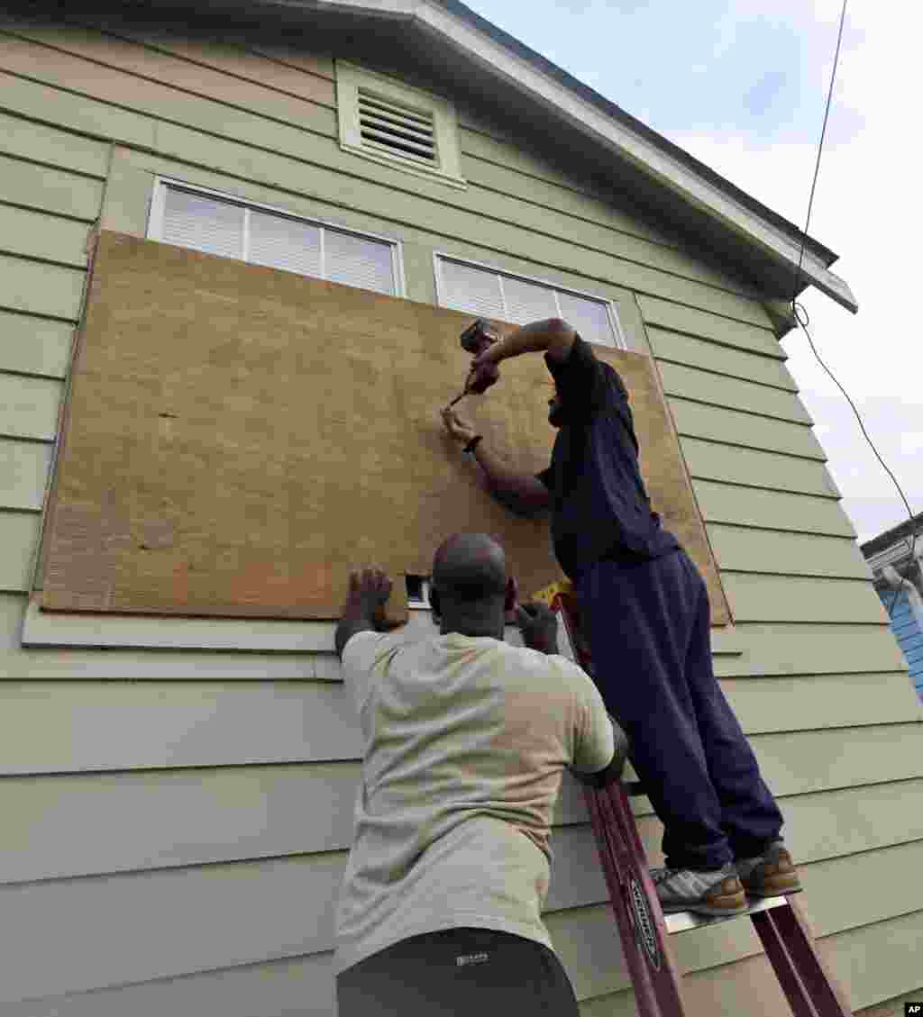 Stacey Davis, left, and his brother board up windows on their home before Tropical Storm Isaac hits Aug. 28, 2012, in New Orleans.