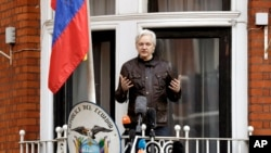 FILE - WikiLeaks founder Julian Assange gestures as he speaks on the balcony of the Ecuadorian embassy, in London, May 19, 2017.