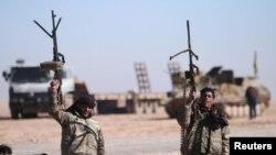 ARSIP - Pejuang Syrian Democratic Forces (SDF) mengangkat senjata-senjata mereka di bagiah utara kota Raqqa, Suriah, 3 Februari 2017 (foto: REUTERS/Rodi Said/Arsip)