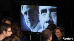 A video screen shows Republican presidential candudate and former Massachussetts Governor Mitt Romney (L) and U.S. President Barack Obama in a campaign video sponsored by the campaign of rival candidate and former U.S. Senator Rick Santorum (Not Pictured)