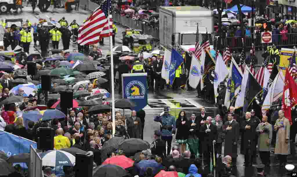 Survivors, families of victims, officials, first responders and guests pause as the flag is raised at the finish line during a tribute in honor of the one year anniversary of the Boston Marathon bombings in Boston, April 15, 2014.