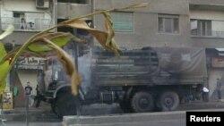 Khói bốc lên từ một chiếc xe tải quân sự của lực lượng chính phủ Syria bị đốt cháy tại Damascus, ngày 18/7/2012