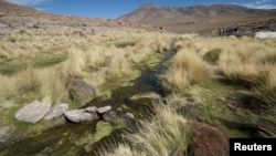 FILE - Water runs in one of the springs in Silala, south of La Paz, March 29, 2016. Chile on Monday filed a lawsuit against neighbor Bolivia, which has long insisted that it should be compensated for use of water flowing down the Silala River into Chile.