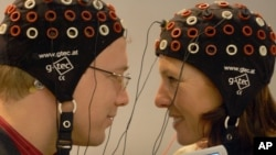 In this file photo, models use a brain computer interface to talk to each other by a laptop computer at the Medica 2006 fair in Duesseldorf, western Germany, Tuesday, Nov.14, 2006. (AP Photo/Frank Augstein)