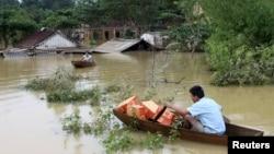 Một người đàn ông chèo thuyền vận chuyển hàng cứu trợ giúp các nạn nhân lũ lụt ở huyện Hương Khê, Hà Tĩnh. (Ảnh tư liệu)