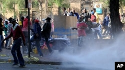 African National Congress Youth League (ANCYL) supporters flee water cannon fire as they took to the streets in downtown Johannesburg in support of leader Julius Malema who is facing a disciplinary hearing by senior ANC leaders. Malema is charged with bri